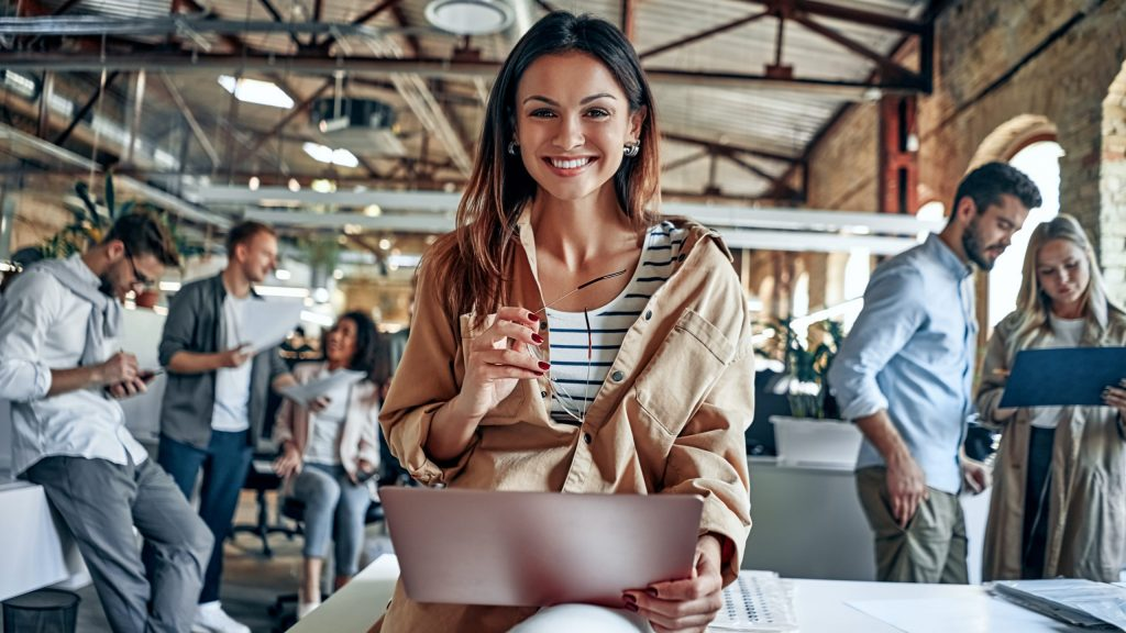 Woman with laptop smiling in an office with people chatting about how to transform workplace talent