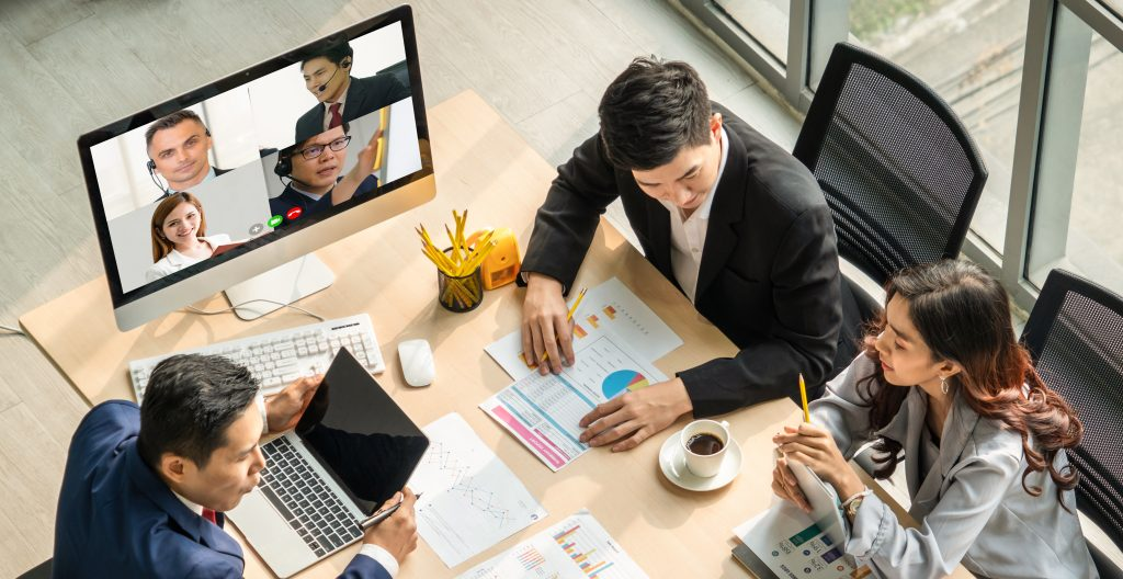 Business people around a table in a video conference.
