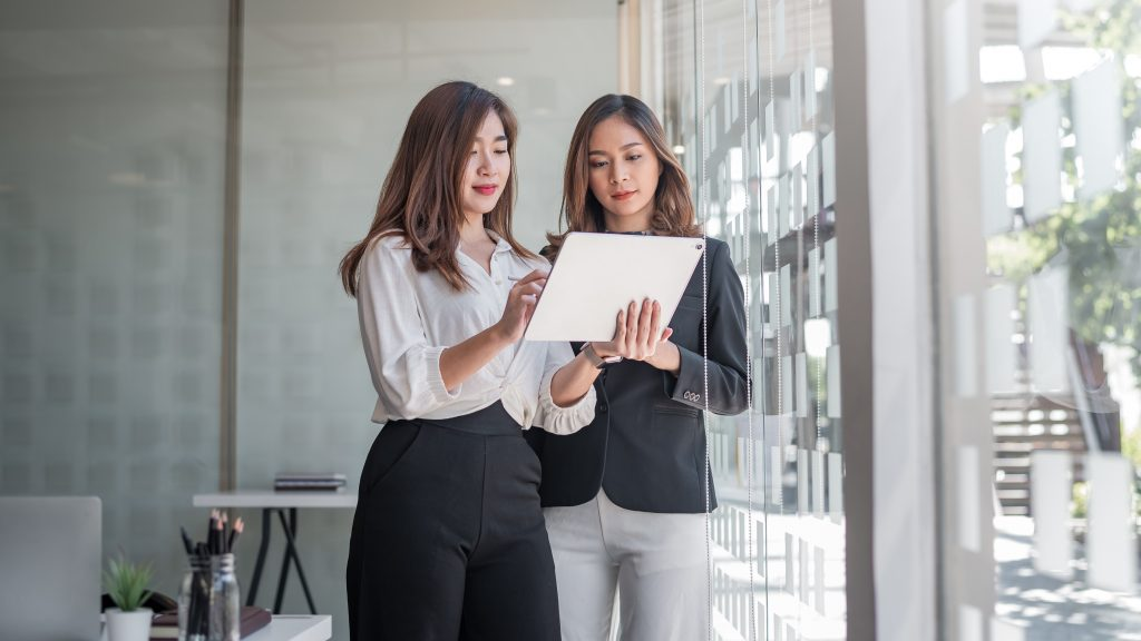 Two asian women standing and looking at a tablet.