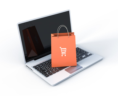 Laptop with bag on top of it having a shopping cart as a decoration symbol.