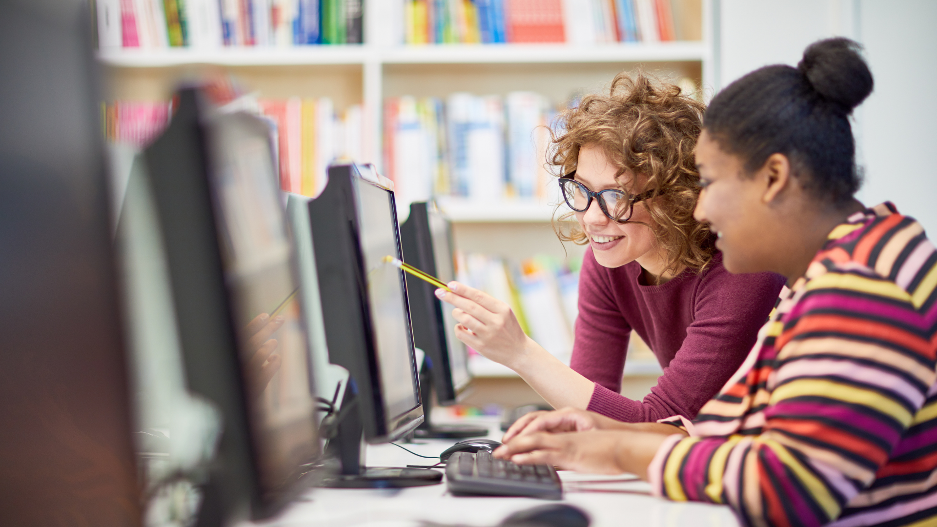 Two women set up a team in SimVenture Validate. They are in a library looking at a computer.